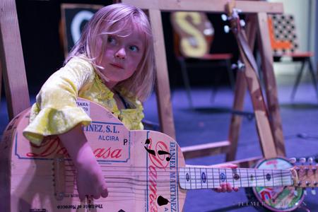 A child playing what looks like a carton made guitar at 'Muziek Raken' photo by: Jelmer Gremmen.