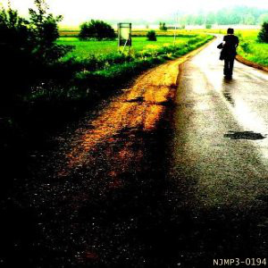 A lonely shadow of a person appears to be standing in the middle of a damp country road in the album art for Step Further Away's self-titled debut.